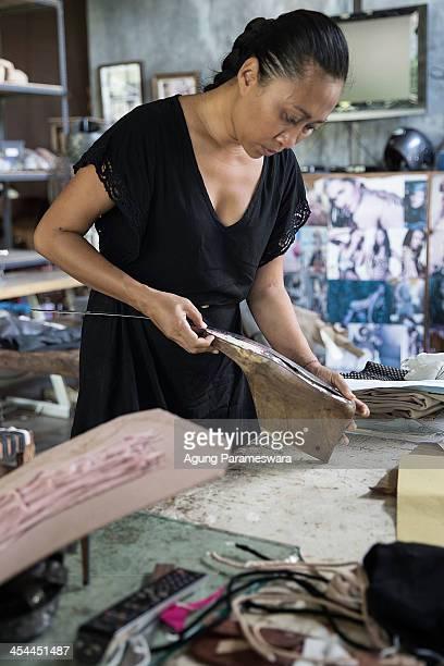 Ni Luh Ayu Pertami the designer and the owner of Niluh Djelantik measures a wooden shoelast at her atelier on November 12 2013 in Canggu Village Bali...
