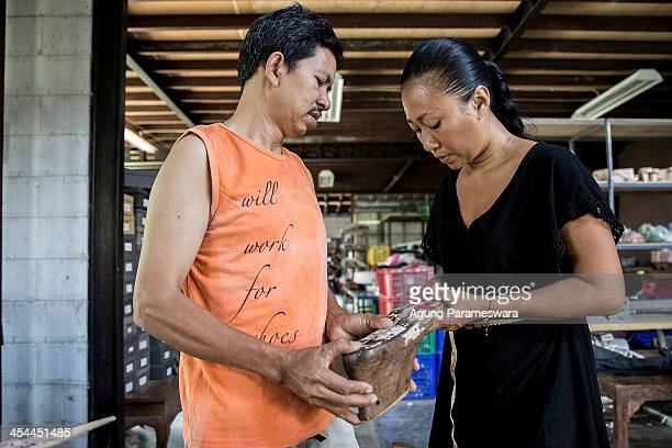 Ni Luh Ayu Pertami the designer and the owner of Niluh Djelantik and staff measure a wooden shoelast at her atelier on November 12 2013 in Canggu...