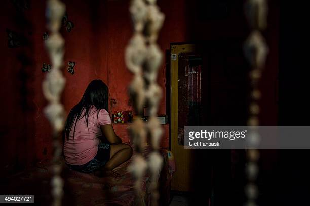 Nia , a commercial sex worker woman sits inside her room at 'Jarak' brothel complex near 'Dolly' on May 25, 2014 in Surabaya, Indonesia. She has...