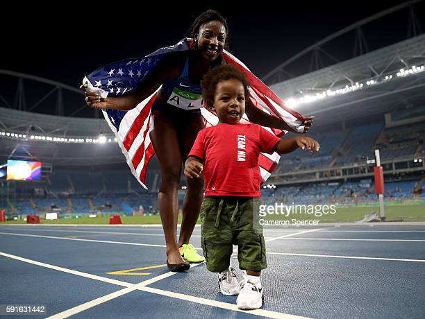 Nia Ali of the United States celebrates with her son Titus after winning the silver medal in the Women's 100m Hurdles Final on Day 12 of the Rio 2016...