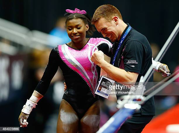 Nia Dennis is congratulated by her coach Christian Gallardo after competing on the uneven bars in the junior women finals during the 2014 PG...