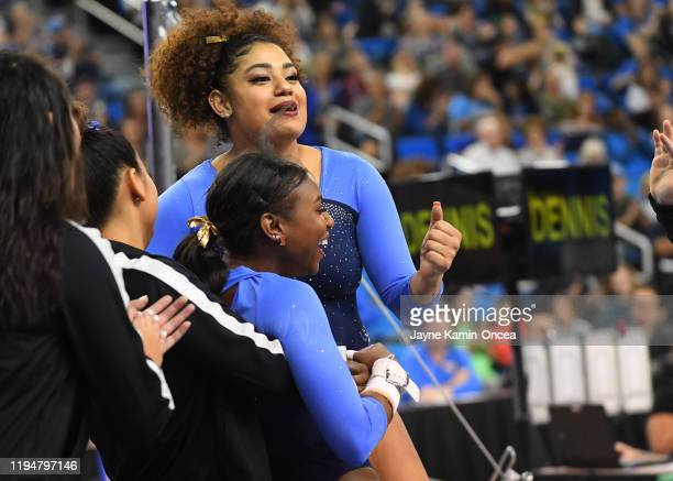 Nia Dennis is congratulated by Sekai Wright after performing on the uneven bars during UCLA Gymnastics Meet the Bruins intra squad event at Pauley...