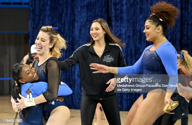 Nia Dennis left hugs teammate Mercedez Sanchez after performing on the Uneven Parallel Bars during the Meet The Bruins gymnastics exhibition in...