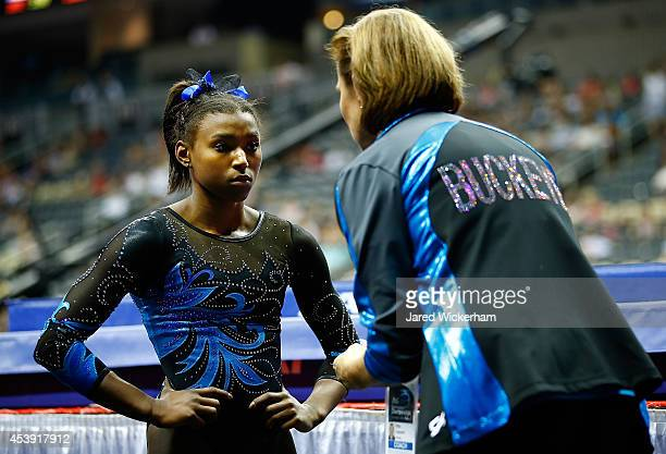 Nia Dennis talks with her coach Kittia Carpenter following her beam routine in the junior women preliminaries during the 2014 PG Gymnastics...