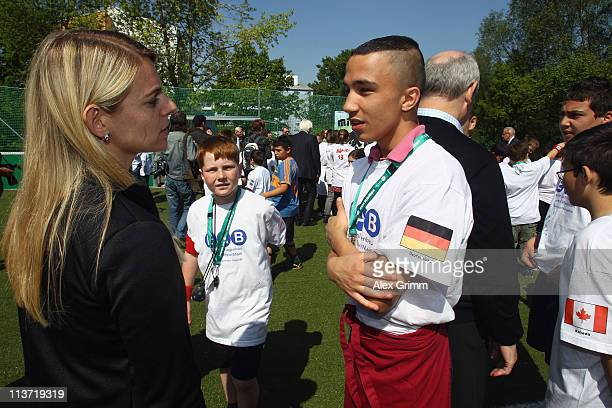 Nia Kuenzer chats with children during the presentation of a DFB Mini Soccer Field at FriedrichFroebelSchule on May 5 2011 in Neu Isenburg Germany