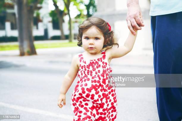 Niña paseando con la mano de un adulto