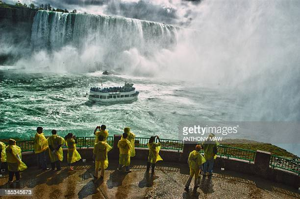 CONTENT] Niagara Falls and the Maid of the Mist tour boat Tourists wear yellow plastic rain capes to keep dry under the mist of the immense waterfalls