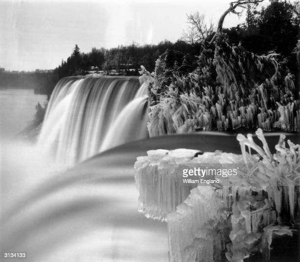 Niagara Falls in winter seen from Goat Island Luna Island stands in the middle of the cascade known as the American or Rainbow Falls and Prospect...