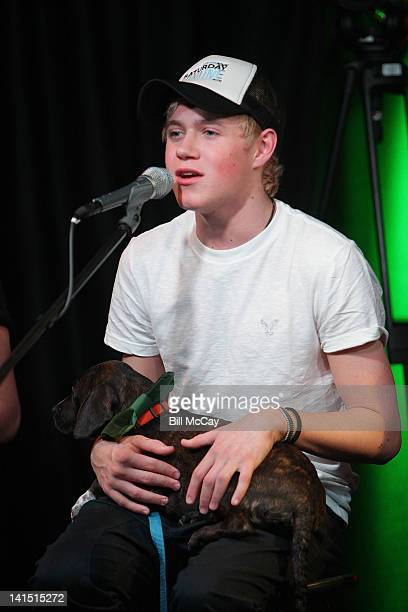 Niall Horan from the band One Direction performs with a puppy from the Delco SPCA at Radio Station Q102 iHeartRadiod Performance Theater March 17,...