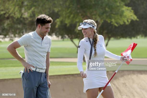 Niall Horan the music artist enjoys a lighthearted moment with Paige Spiranac of the United States during the pro-am as a preview for the Omega Dubai...