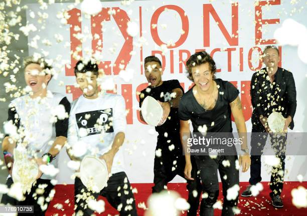 Niall Horan, Zayn Malik, Liam Payne and Harry Styles of One Direction throw popcorn with director Morgan Spurlock at a photocall to launch their new...
