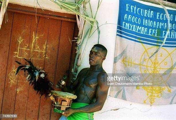 A 'Nianigo' member of the Abacua society knocks on the door of the Abacua temple holding a drum and feather brush during a twoday initiation rite for...
