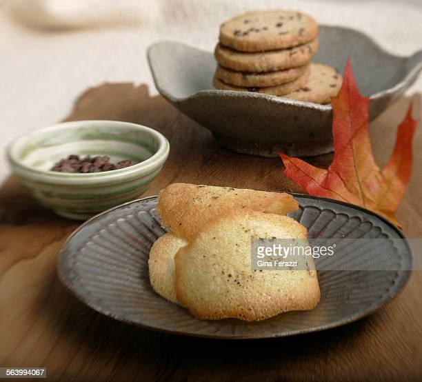 Nibby Whale Wheat Sable cookies and Corn Tuiles with salt and pepper on a rustic board