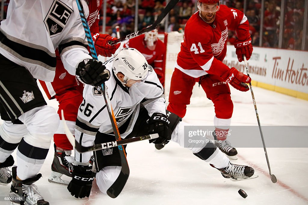 Nic Dowd #26 of the Los Angeles Kings tries to control the puck next to Luke Glendening #41 of the Detroit Red Wings during the third period at Joe Louis Arena on December 15, 2016 in Detroit, Michigan. Los Angeles won the game 4-1.