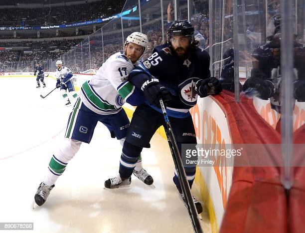 Nic Dowd of the Vancouver Canucks and Mathieu Perreault of the Winnipeg Jets battle along the boards as they keep an eye on the play during first...