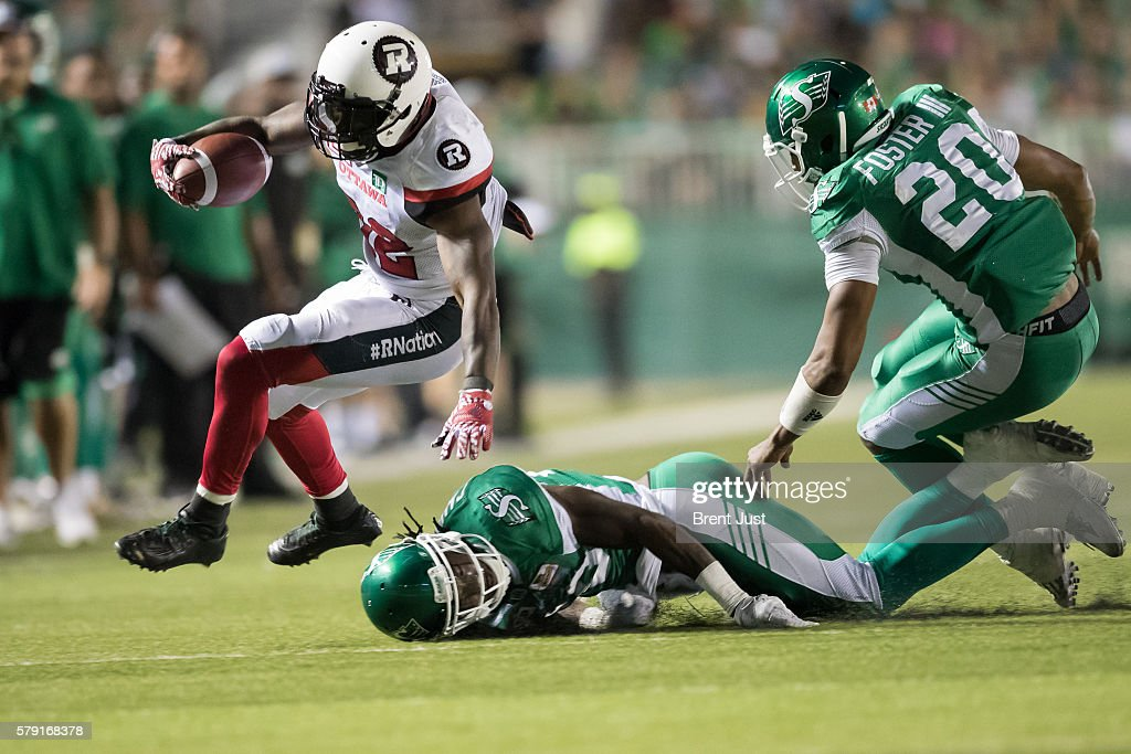 Nic Grigsby #32 of the Ottawa Redblacks jumps over a Saskatchewan Roughrider defender in the game between the Ottawa Redblacks and the Saskatchewan Roughriders at Mosaic Stadium on July 22, 2016 in Regina, Canada.