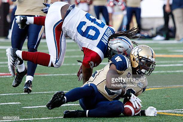Nic Grigsby of the Winnipeg Blue Bombers is tackled by Jerald Brown of the Montreal Alouettes during the CFL game at Percival Molson Stadium on July...