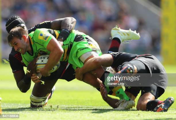Nic Groom of Northampton Saints is tackled by Schalk Brits and Maro Itoje of Saracens during the Aviva Premiership match between Saracens and...