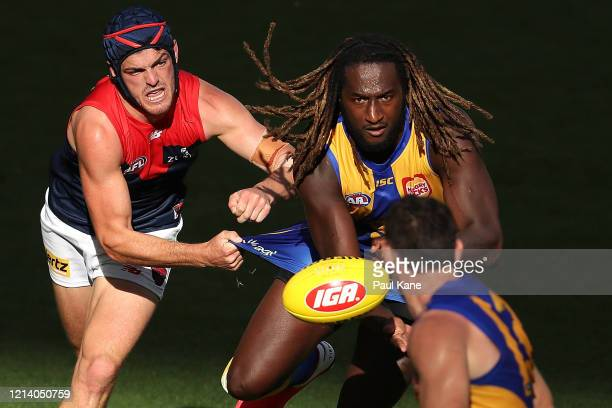 Nic Naitanui of the Eagles gets his handball away while being tackled by Angus Brayshaw of the Demons during the round 1 AFL match between the West...