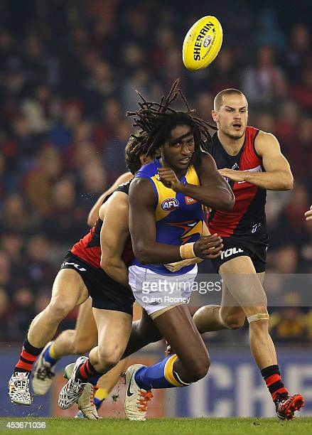 Nic Naitanui of the Eagles handballs whilst being tackled during the round 21 AFL match between the Essendon Bombers and the West Coast Eagles at...