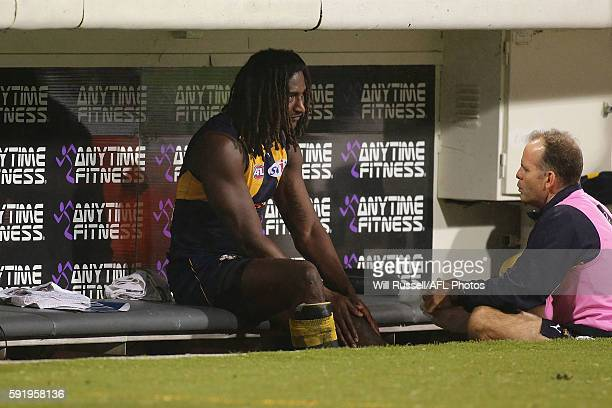 Nic Naitanui of the Eagles holds his left leg while resting on the bench during the round 22 AFL match between the West Coast Eagles and the Hawthorn...