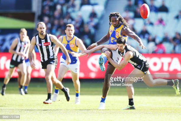Nic Naitanui of the Eagles kicks the ball past Scott Pendlebury of the Magpies during the round 17 AFL match between the Collingwood Magpies and the...