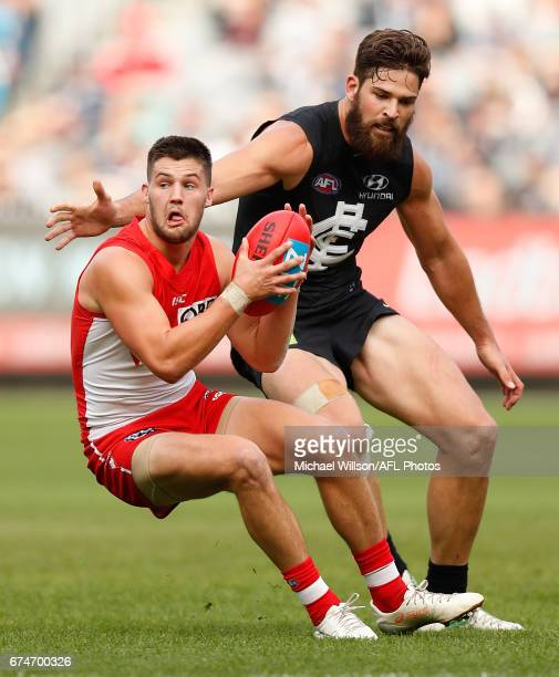 Nic Newman of the Swans evades Matthew Kreuzer of the Blues during the 2017 AFL round 06 match between the Carlton Blues and the Sydney Swans at the...