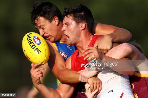 Nic Newman of the Swans is tackled by Hugh McCluggage of the Lions during the AFL JLT Community Series match between the Brisbane Lions and the...