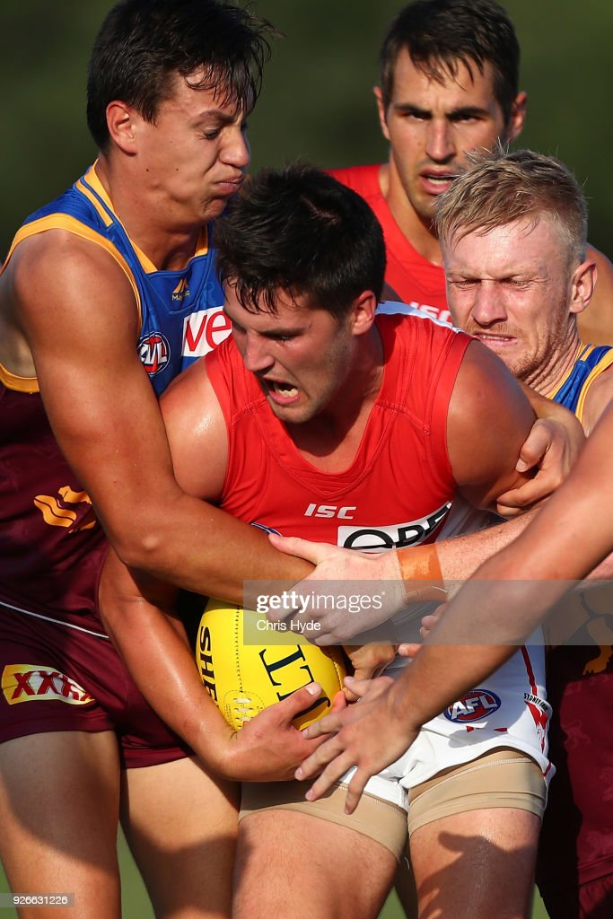 Nic Newman of the Swans is tackled by Hugh McCluggage of the Lions during the AFL JLT Community Series match between the Brisbane Lions and the Sydney Swans at Moreton Bay Central Sports Complex on March 3, 2018 in Brisbane, Australia.