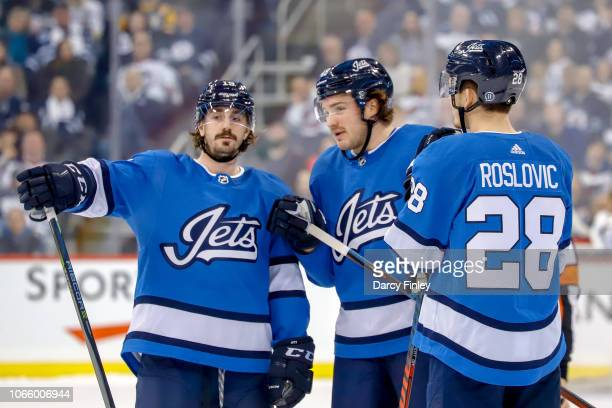 Nic Petan Brendan Lemieux and Jack Roslovic of the Winnipeg Jets discuss strategy during a second period stoppage in play against the Pittsburgh...