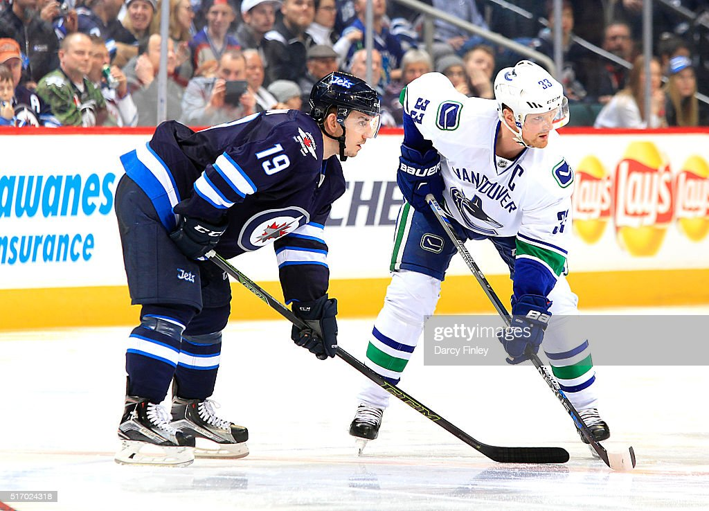 Nic Petan #19 of the Winnipeg Jets and Henrik Sedin #33 of the Vancouver Canucks get set for a third period face-off at the MTS Centre on March 22, 2016 in Winnipeg, Manitoba, Canada.
