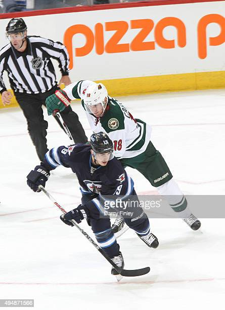Nic Petan of the Winnipeg Jets and Ryan Carter of the Minnesota Wild follow the play up the ice during second period action at the MTS Centre on...