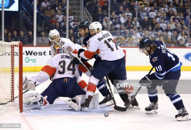 Nic Petan of the Winnipeg Jets plays the loose puck as goaltender James Reimer of the Florida Panthers gets turned around in the crease during first...