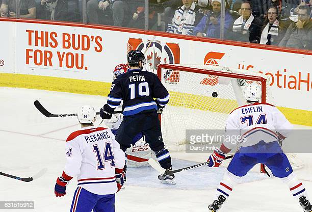 Nic Petan of the Winnipeg Jets Tomas Plekanec and Alexei Emelin of the Montreal Canadiens watches as the puck flies into the net for a second period...