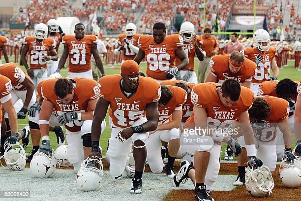 Nic Redwine of the Texas Longhorns with teammates kneel on the field before the game against the Arkansas Razorbacks on September 27, 2008 at Darrell...