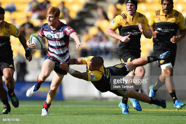 Nic Stirzaker of the Melbourne Rebels is tackled by TJ Perenara of the Hurricanes during the round two Super Rugby match between the Hurricanes and...