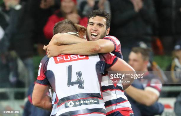Nic Stirzaker Steven Cummins and Jack Debreczeni of the Rebels celebrate at the full time whistle as they win the round eight Super Rugby match...