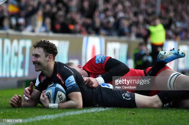 Nic White of Exeter Chiefs beats Nick Isiekwe of Saracens to score his sides first try during the Gallagher Premiership Rugby match between Exeter...