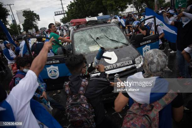 People attack a police car during a demonstration against the government At least one person was injured in Managua when strangers fired guns at...