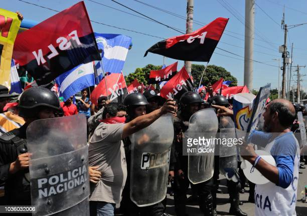 Nicaraguan 62yearold marathon runner Alex Vanegas confronts Sandinista supporters standing behind riot police during the 'Ballons March' against the...