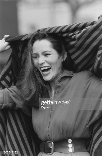 Nicaraguan American actress Barbara Carrera laughing as she holds a striped shawl up behind her head during a photo call to promote promote her...