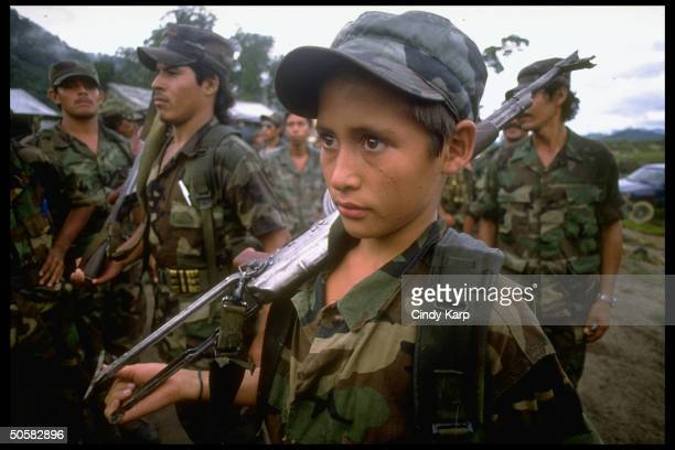 Nicaraguan contra rebels incl rifle toting youngster at/nr camp in Yamales Honduras