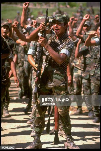 Nicaraguan contra rebels raising clenched fists shouting wearing fervent expressions at/nr camp in Yamales Honduras