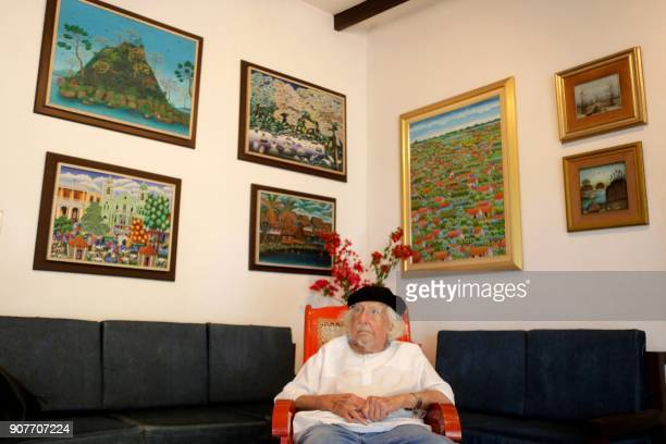 Nicaraguan poet and priest Ernesto Cardenal signs books in his house during his 93rd birthday anniversary in Managua on January 20 2018 Cardenal is...