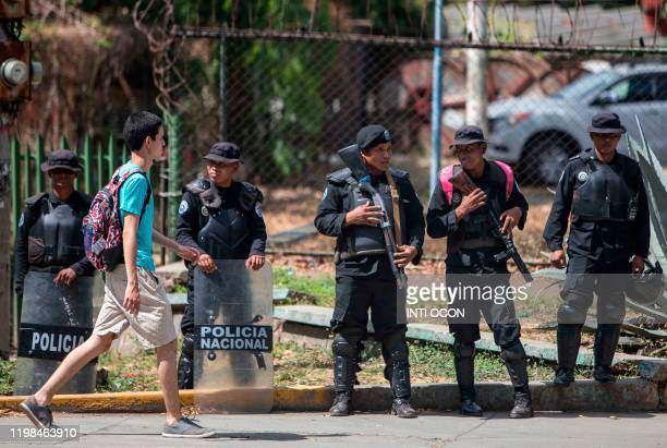 Nicaraguan police members stand guard during a university students protest demanding Nicaraguan President Daniel Ortega's government the political...