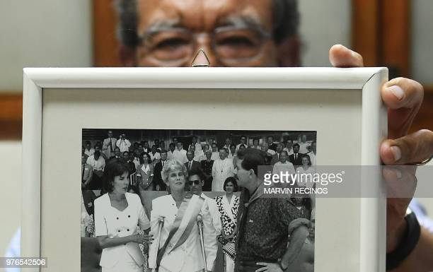 Nicaraguan politician Edmundo Jarquin shows a 1990 photo of the then outgoing President Daniel Ortega and the then new President Violeta Chamorro...