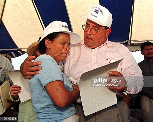 Nicaraguan President Arnoldo Aleman holds the deed, or title of property, of a Hurricane Mitch victim in Posoltega, Nicaragua 05 March. El presidente...