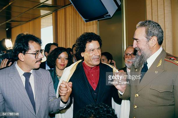 Nicaraguan President Daniel Ortega Libyan Statesman Moammar Kadhafi and Cuban Head of State since 1976 Fidel Castro join hands at the eighth Summit...