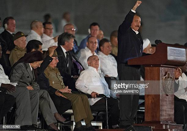 Nicaraguan President Daniel Ortega raises his fist as he delivers a speech next to Cuban President Raul Castro Venezuela's President Nicolas Maduro...