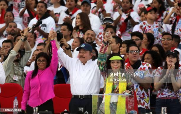 Nicaraguan President Daniel Ortega raises his wife, Vice-President Rosario Murillo's and Venezuelan Vice-President Delcy Rodriguez's hands, during...